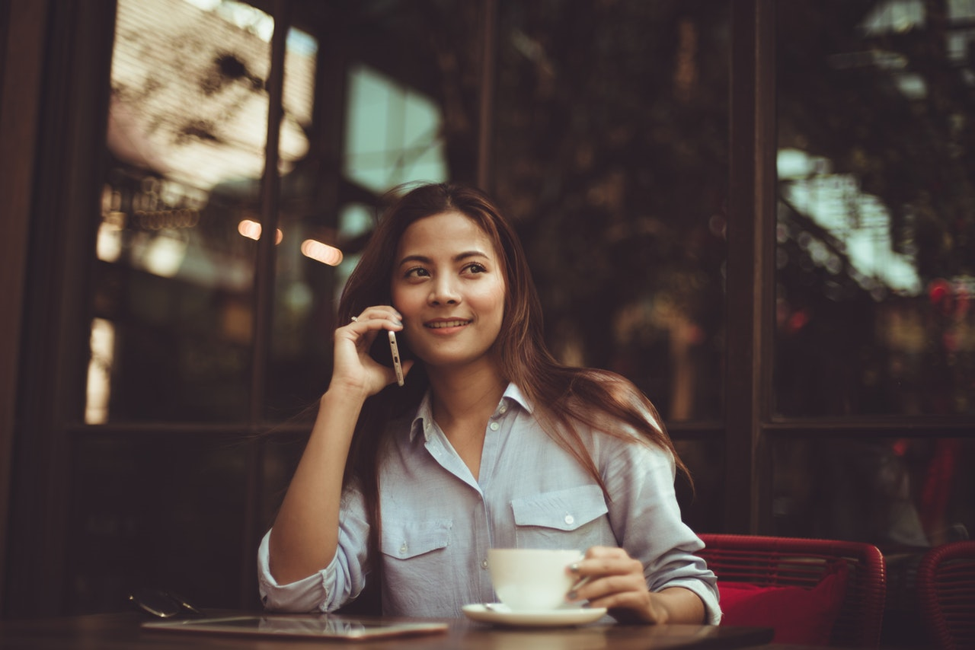 smiling woman sitting at table holding phone to her ear in right hand and holding white coffee cup in her left hand