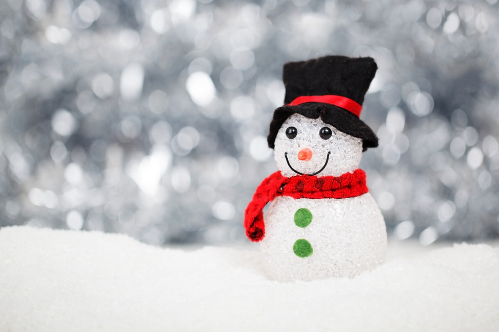 toy snowman with black hat red scarf and green buttons sitting on snow in front of shiny background