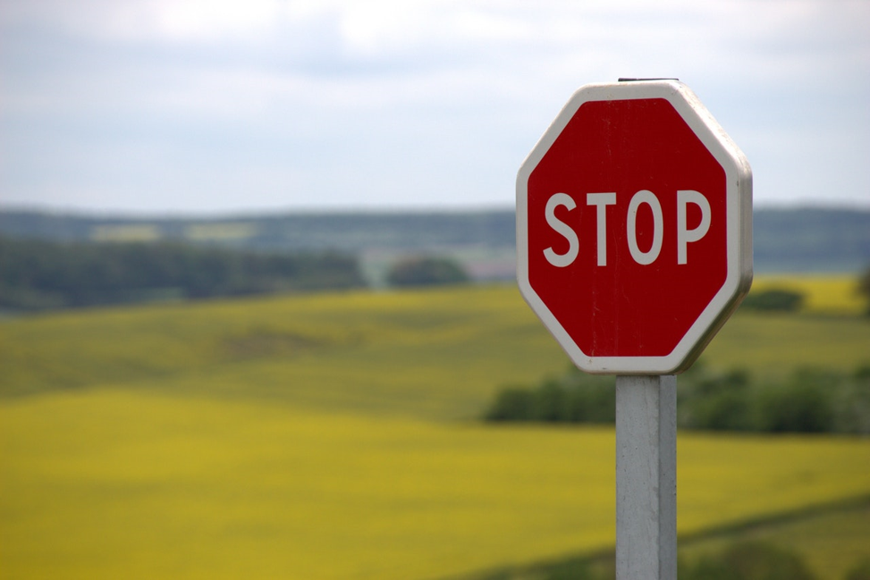 stop sign in front of a large meadow.