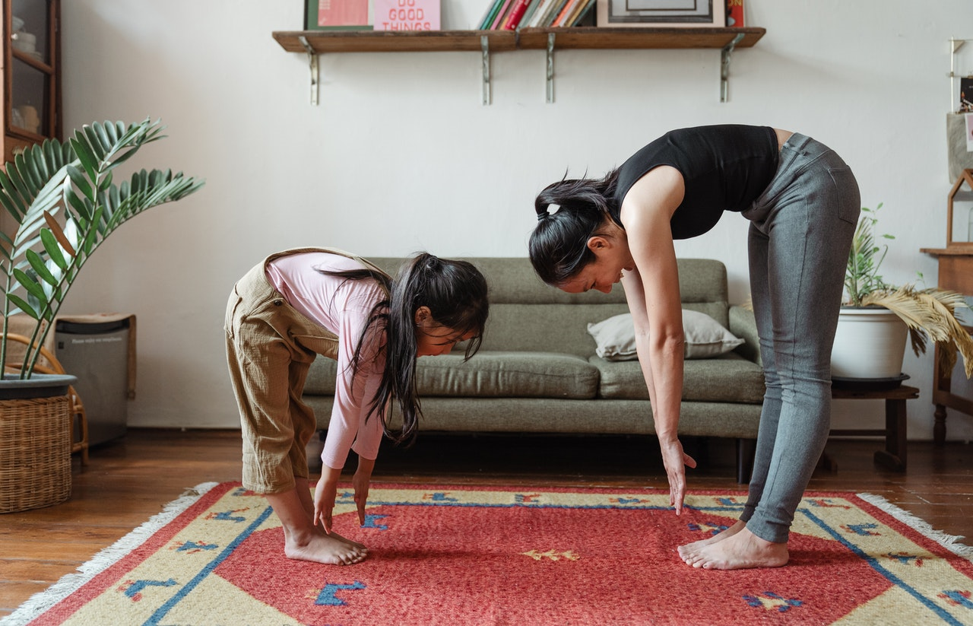 Two people stretching in their living room.