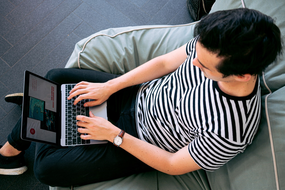 Person wearing striped shirt researching cash advance loans on their computer.