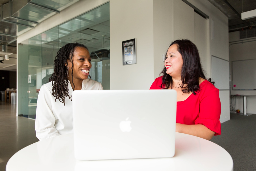 two smiling women sitting at table next to open MacBook in office.