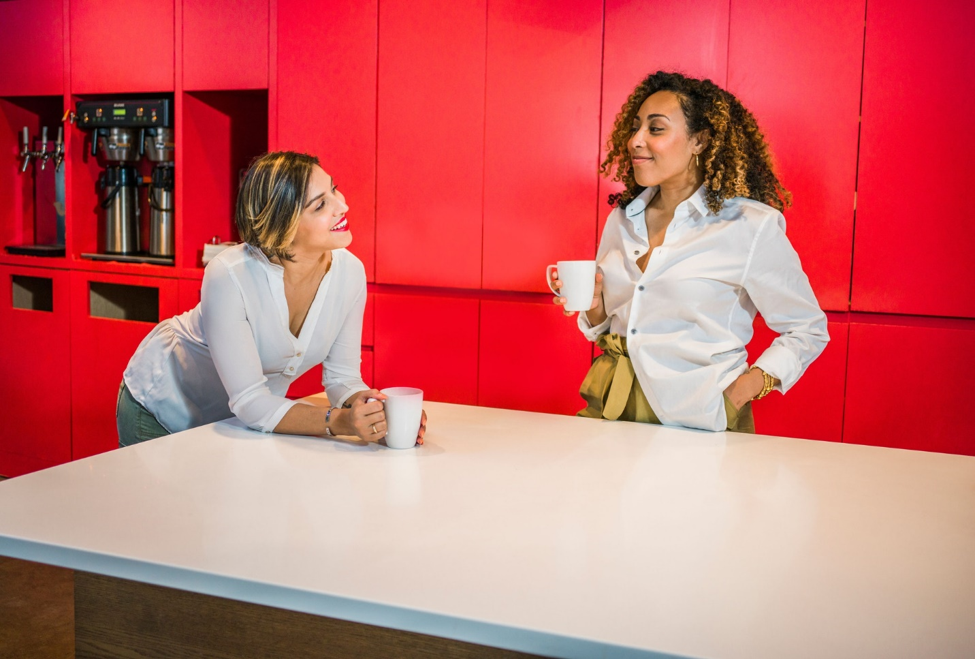 two women in white blouses smiling at each other while holding white coffee mugs next to white counter in red break room.