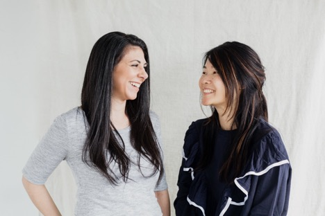 two smiling women with long dark hair standing next to each other in front of white backdrop