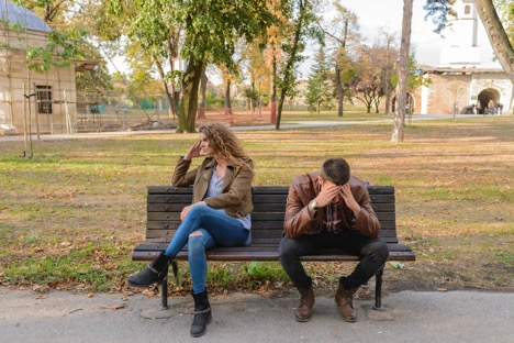 upset woman looking to the right on a wooden bench next to man holding his head in his hands in a park