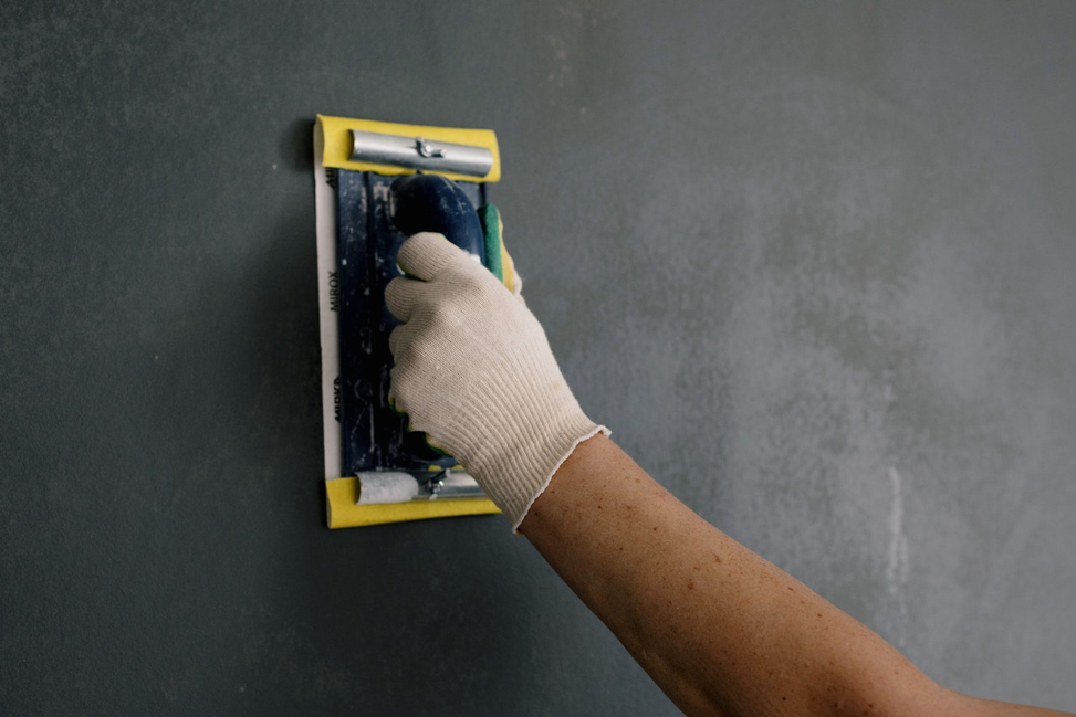 Person repairing the drywall in their home.