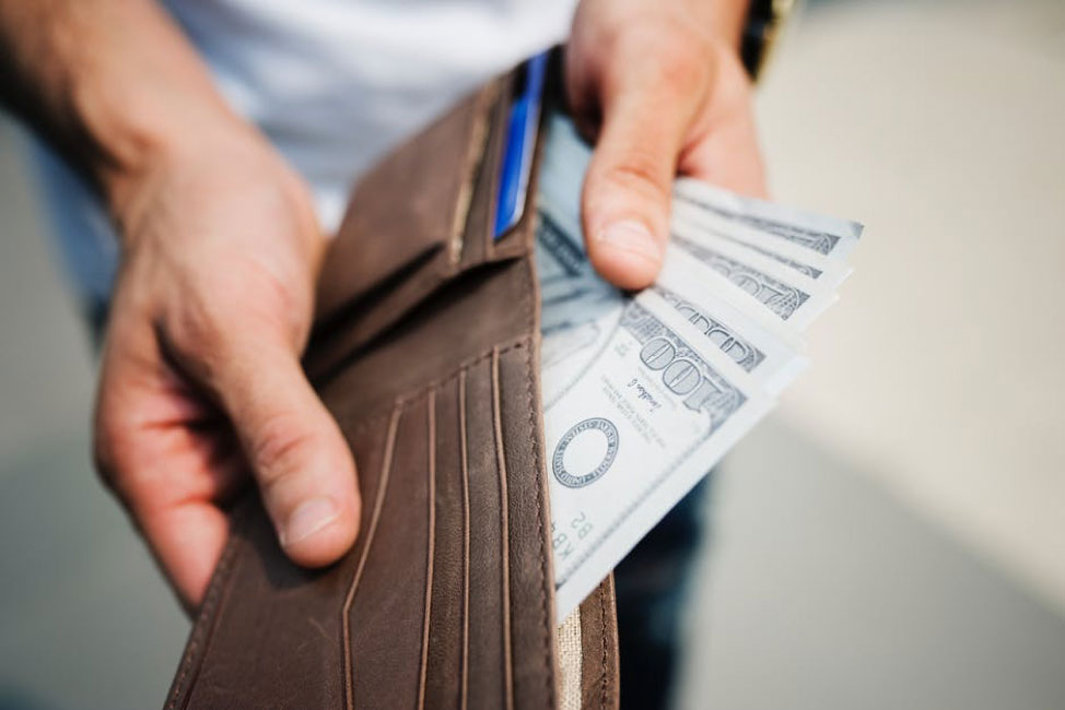 Cropped image of hands taking out money from wallet