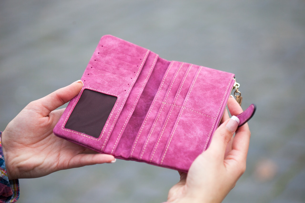person holding empty pink wallet