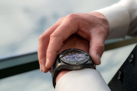 man touching the face of a grey analogue wrist watch that's on his left wrist with his right hand