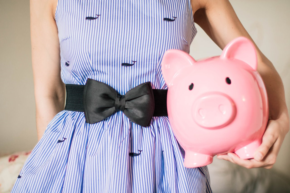 person in a dress holding piggy bank