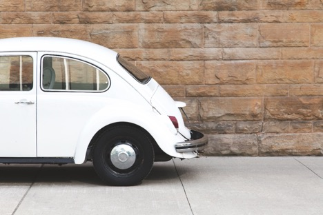 half of a white vintage Volkswagen bug on a sidewalk in front of a brick wall