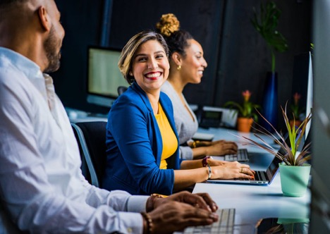 woman in blue blazer and yellow shirt typing on laptop while smiling to person on her right