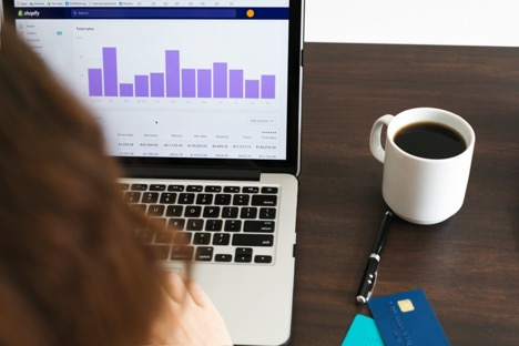 over-the-shoulder shot of person looking at laptop next to pen credit cards and mug of coffee on table