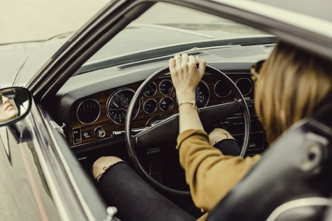 woman in ripped black jeans and brown shirt holding the driving wheel of a car with her left arm