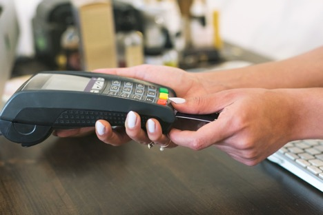 woman holding POS machine in right hand while inserting card into reader with left
