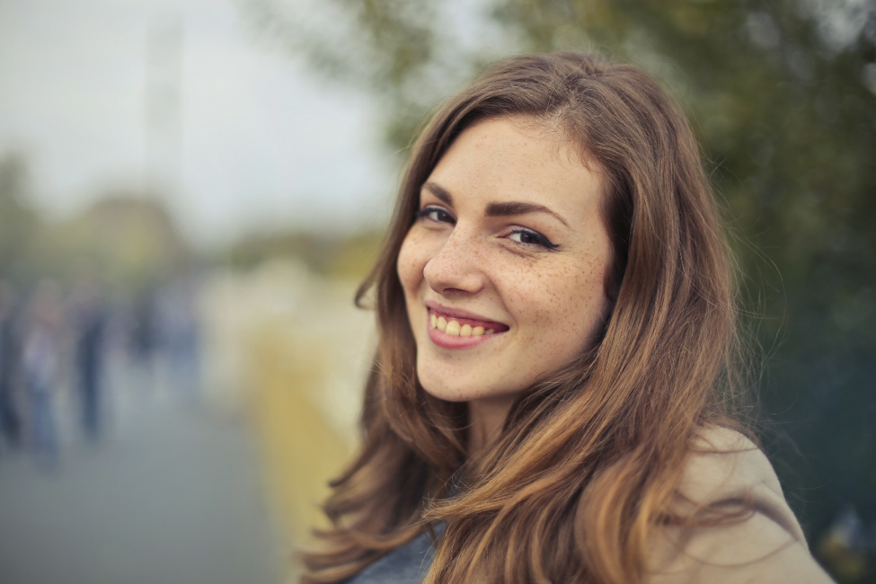 woman with long hair smiling outside