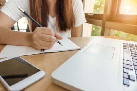 close up of laptop and phone resting on table where a woman is writing in a notebook with a pencil